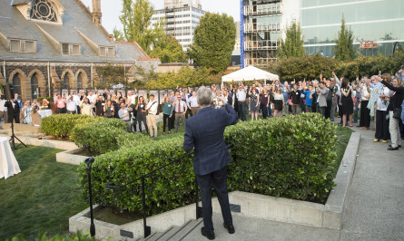 Crowd toasting outdoors for Hennebery Eddy Architects 25th anniversary celebration