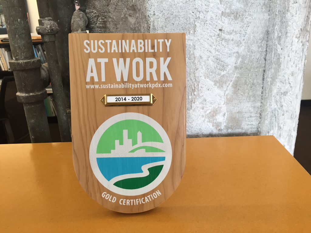 Wood plaque showing Sustainability at Work Gold certification for Hennebery Eddy Architects