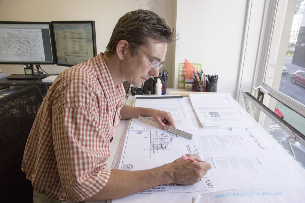 In-house specifications writer at Hennebery Eddy Architects examining architectural drawings at a desk.