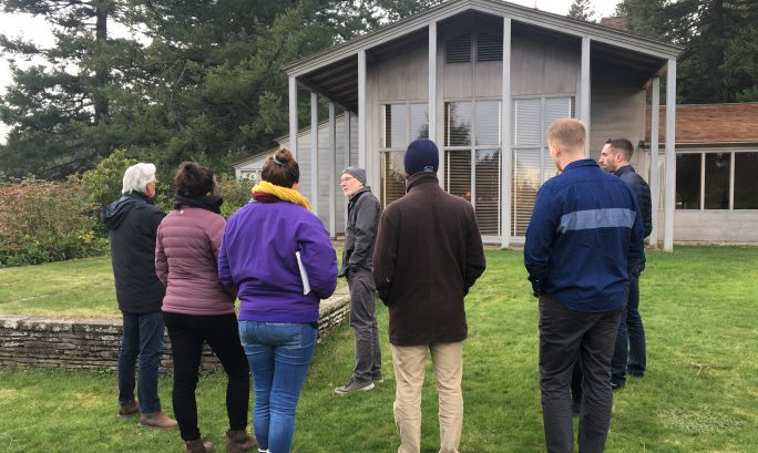 A group of young adults stand on the lawn outside of a the Aubrey Watzek House, an example of Pacific Northwest regional Modernism.