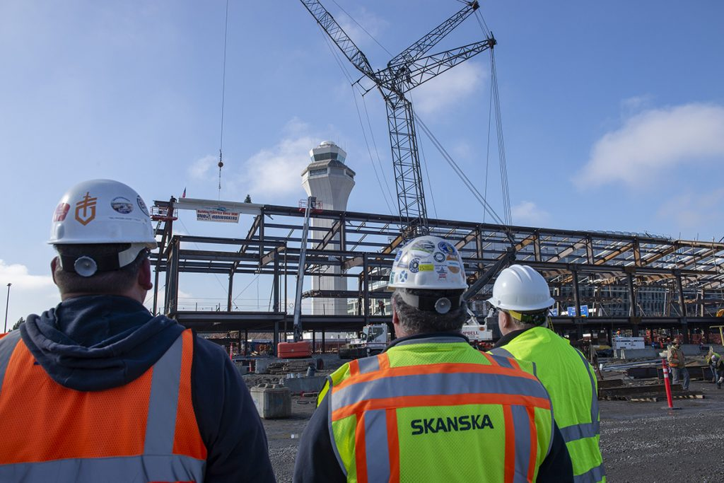Construction workers watch a steel beam being placed by a crane at Portland International Airport.