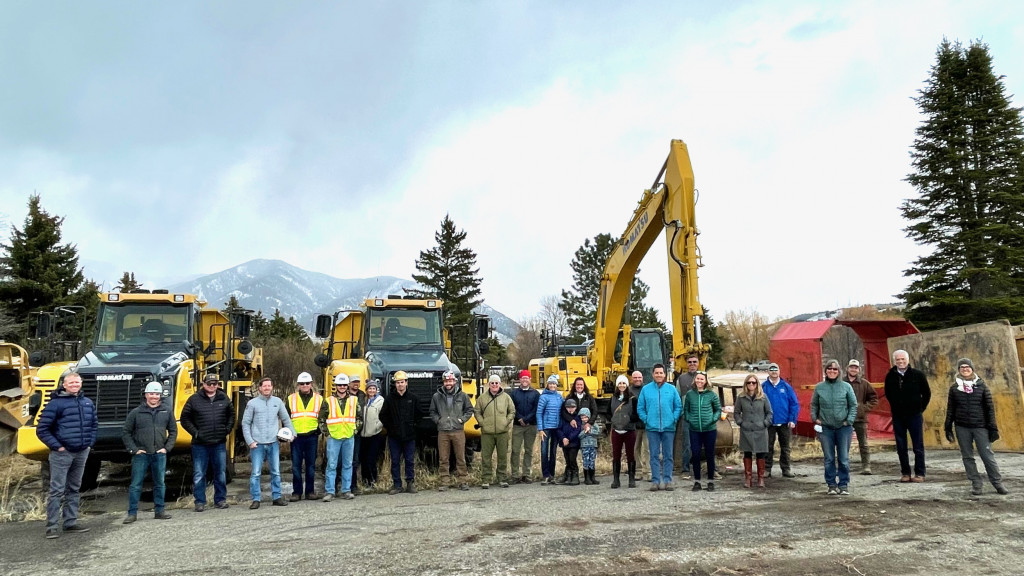 A group of people stand in front of an excavator and other heavy equipment, facing the camera.